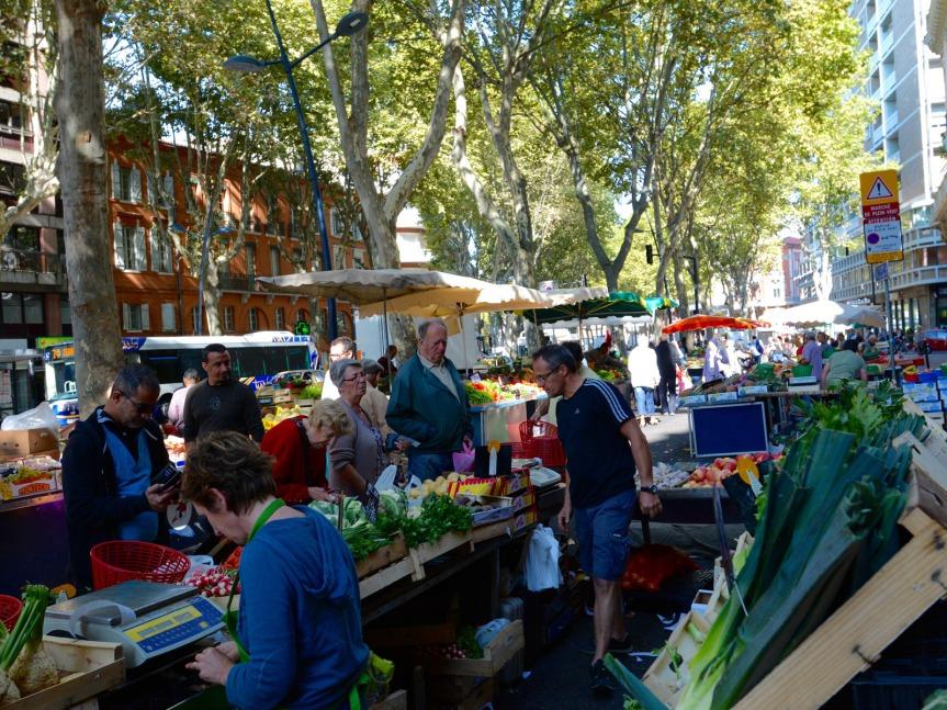 Le marché du Cristal. Le ruban des étals, frais et coloré, s'étire sous le couvert des grands platanes du boulevard de Strasbourg.